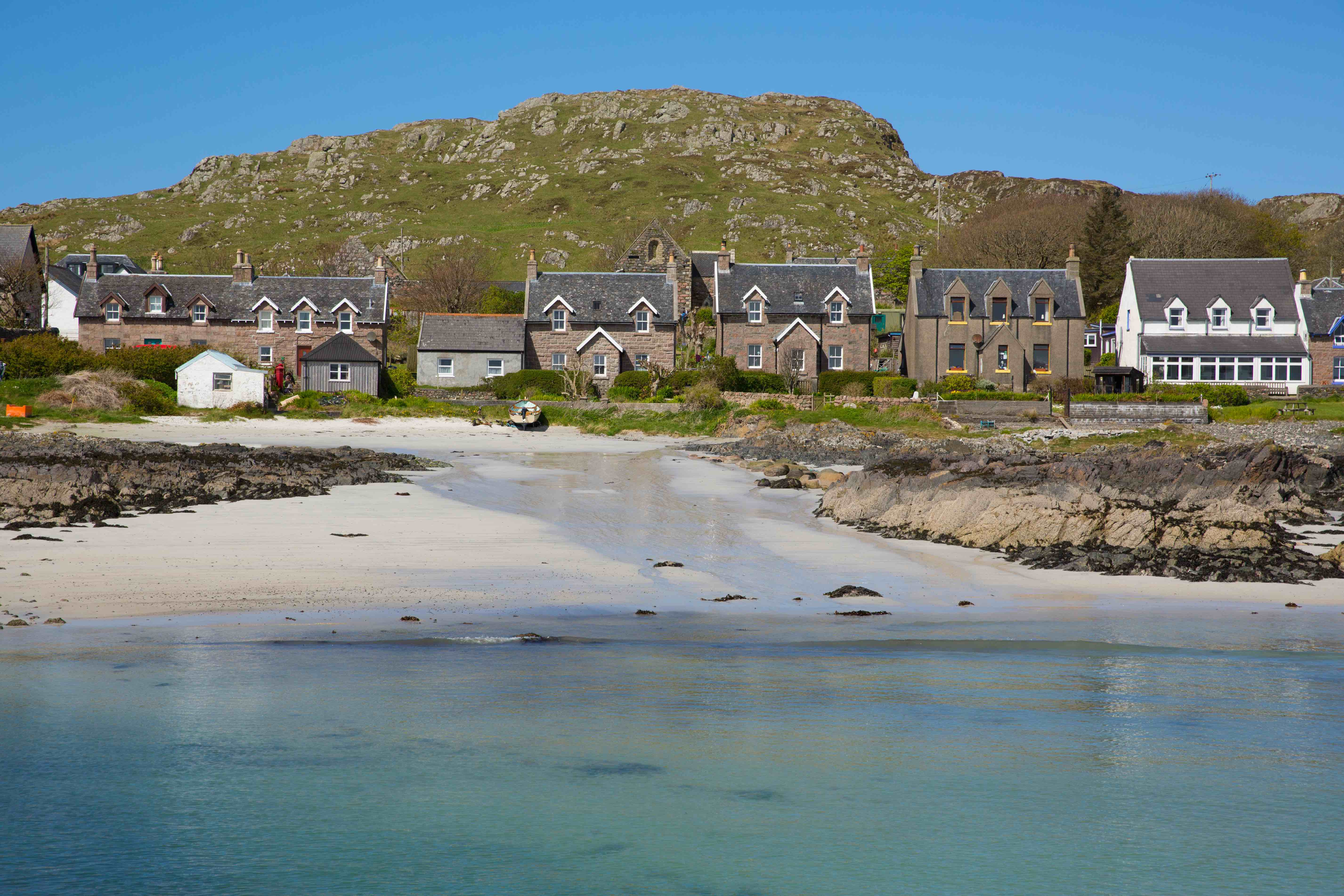 Clear blue sky hangs over the houses of the tiny Scottish island of Iona.
